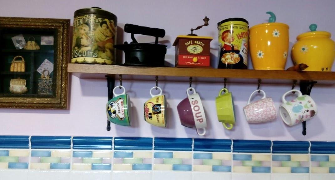 Balda de madera de la que cuelgan tazas de diferentes tamaños y colores. Encima hay dos tarros , dos botes, una plancha y un molinillo antiguos.