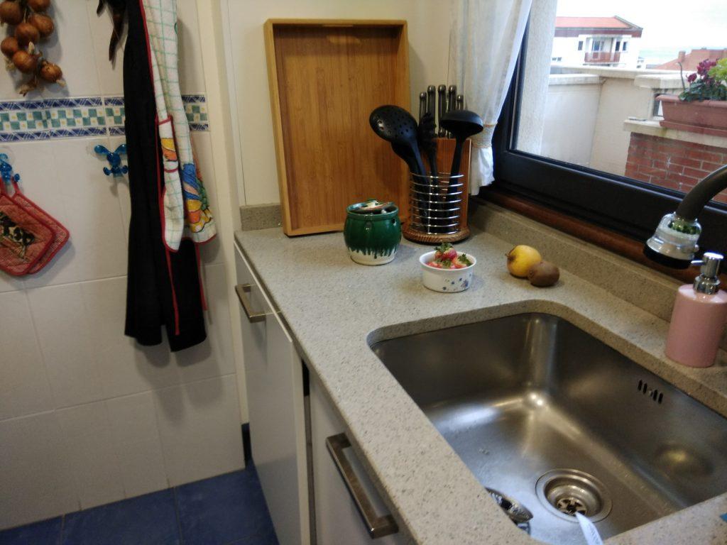 Zona de agua de la cocina. con su impoluto fregadero situado debajo de la ventana.
